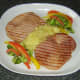 Apple and pineapple sauce is plated with gammon steaks