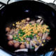 Peas and sweetcorn are added to wok