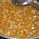 Step eight: Once you get the proper consistency, add peanuts into the jaggery syrup. Boil together for 1 minute.