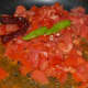 Step one: Saute green chili, red chili, and tomatoes in some oil.