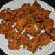Step six: Transfer the cooked pakoras to a plate lined with an absorbent paper.