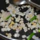 Step 3: Heat oil in a deep-bottomed pan. Throw in chopped onions, ginger, and green chilies. Saute until onions become golden brown.