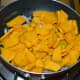 Step two: Add thinly sliced pumpkin. Continue to saute for 1 minute.