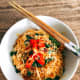 Place the noodles in a bowl. Garnish with thinly sliced peppers and fried shallots. Serve immediately.