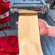 Without folding the dough, pass it through the next setting on the pasta machine. Keep reducing the space between the rollers after each pass.