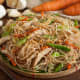 Bihon guisado: Thin rice noodles cooked in a wok with soy sauce, vegetables, and meat.