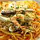 Pancit luglog: Thick rice noodles softened in hot water, stirred in a thickened shrimp sauce, and topped with steamed shrimp, hard-boiled egg, smoked fish, squid, and chopped pechay baguio.