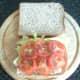 Lettuce on tomato are laid on bread and seasoned
