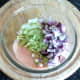 Shredded lettuce and diced red onion are added to chilli sauce