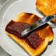 Spread the coconut jam on the crispy toast.