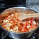 Add the diced onion, red pepper, tomato, paprika and salt to the pan and stir well.