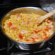 Bring the sauce to a gentle simmer and continue stirring until the onions are golden in color.