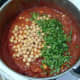 Chickpeas and coriander are added to chicken curry