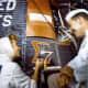 Wally Schirra observes as Cece Bibby paints the Sigma 7 logo. Photo courtesy of NASA.
