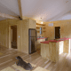 This kitchen demonstrates the heavy emphasis on natural wooden surfaces integrated into the rustic-feeling interior design. Those panels under the dog are under-floor storage.