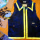 Use a hot glue gun to attach yellow ribbon along the edge and collar of the vest.