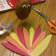 Cut out feathers from construction paper. Tape together in a fan shape and attach to back of potato using peanut butter.