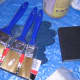 Paintbrushes, sanding block, and gloves.