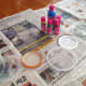 Cover work area with newspaper.  Gather 1 small glass jar, and 5 shallow plastic lids to hold the 5 colors of fabric paint.