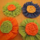 Rosettes embellished with rolled flowers made from crepe paper.