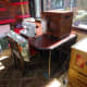 Repurposed table in situ with sewing machine and overlocker in its protective box laid on table top.