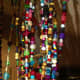 My own beaded curtain is made of glass, plastic and handmade polymer beads, along with fabric to fill in spaces, all threaded with fishing line.