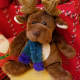 A plush reindeer perches on a basket that's too large for the tree.