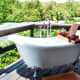 One of the free standing open air bathtubs on a wooden deck of one of the rooms