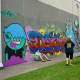 People admiring graffiti murals across from Baldwin Park