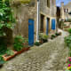 A narrow cobblestone street, weaving between old stone houses that seem unchanged for hundreds of years.