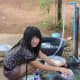 Alisa does the daily chore of dish washing. Water isn't a problem in the village; but hot showers do require a kettle!