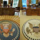 """New York Magazine referred to the Obama Oval Office rug (right) as the """"less-optimistic rug"""" as compared to the rug from George W. Bush's Oval Office (left) with its radiant lines that move out from the presidential seal."""