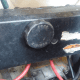 The electrical box located under the seat, attached to the back wall. You can see the positive battery connections entering and exiting the bottom portion of the box.