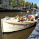 Cruising the canals of Amsterdam with a drink in hand.
