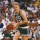 Larry Bird dribbling all the way towards the basket.