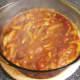 Bhuna sauce is poured over chicken legs in casserole dish