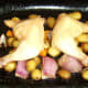 Roasted chicken legs and vegetables are removed from the oven