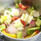 Bell peppers, onion, celery and seasoning are added to pot