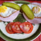 Ready to eat for breakfast. Strammer Max with pickled gherkins and tomatoe slices.