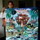 An arpillerista proudly displays her large arpillera of Noah's ark.