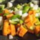 Sweet potato and veggies mixed in the pan.