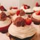 Chocolate cupcakes with vanilla frosting, freshly sliced strawberries, and hazelnut Ferrero Rocher chocolate