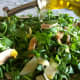 Pouring extra virgin olive oil over the salad