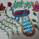 Finish the Madhubani decoration with golden lace for outlining the tail and with blue stones for the feathers. Complete decorating flowers with pearls and stones.