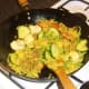 Vegetables are stirred in to spiced duck and rice