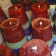 Batches of coloured candles made from plastic cup moulds.