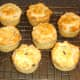 Mini haggis and clapshot puff pastry pies are rested on a wire rack