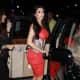 Kim Kardashian in a pretty red dress and high heels