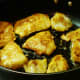 Photo of sautéing the lightly battered fillets of fish in a non-stick skillet on top of the stove.