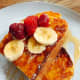 Homemade Italian white bread French toast served with fresh sliced banana, raspberries, and maple syrup